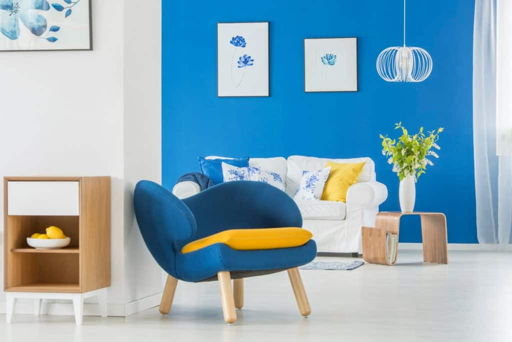 A blue accent wall with a white sofa and a blue accent chair in the living room