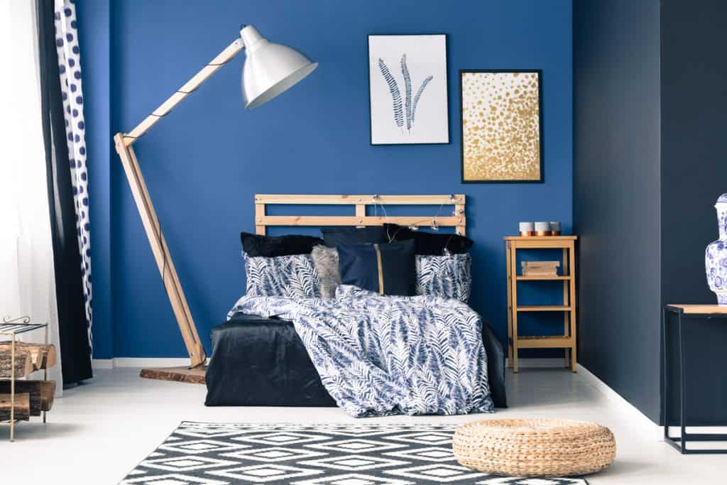 A blue and gray themed bedroom with a wooden bed and huge standing lamp on the side