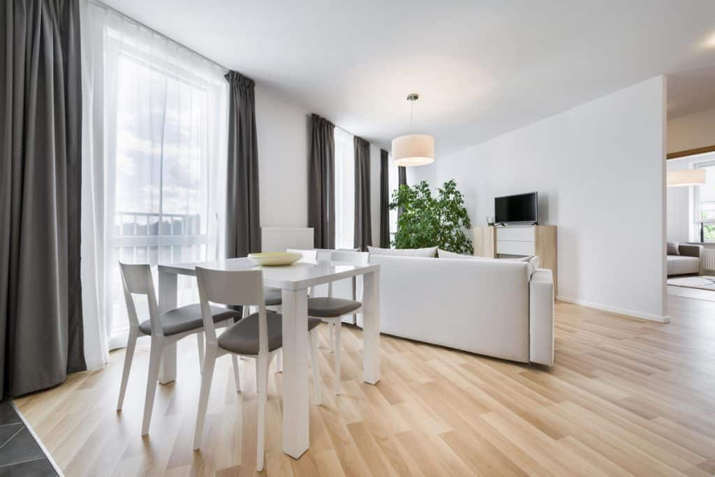 A combined dining and living room with laminated wooden flooring and huge windows with gray and white curtains