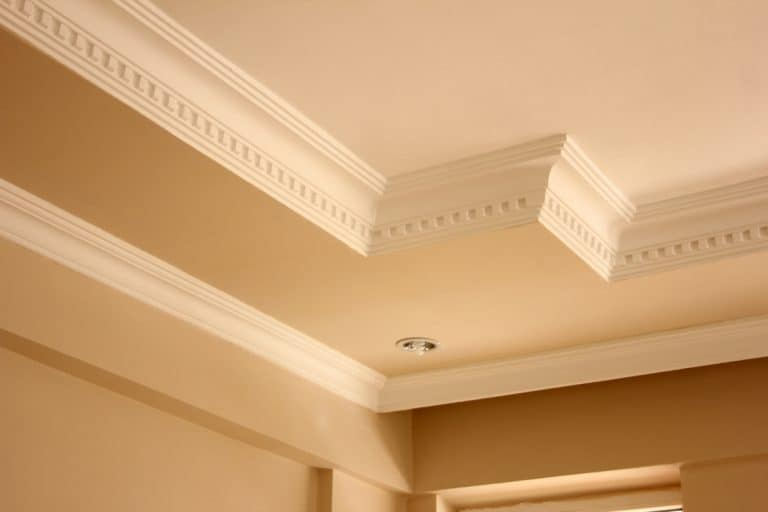 A crown molding in living room painted with cream paint with light brown painted wall, What Rooms Should Have Crown Molding?