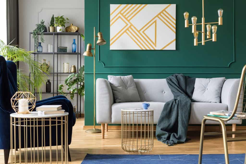 A dark green colored wall with a white sofa next to the wall incorporated with gold plated metal furnitures and chandelier