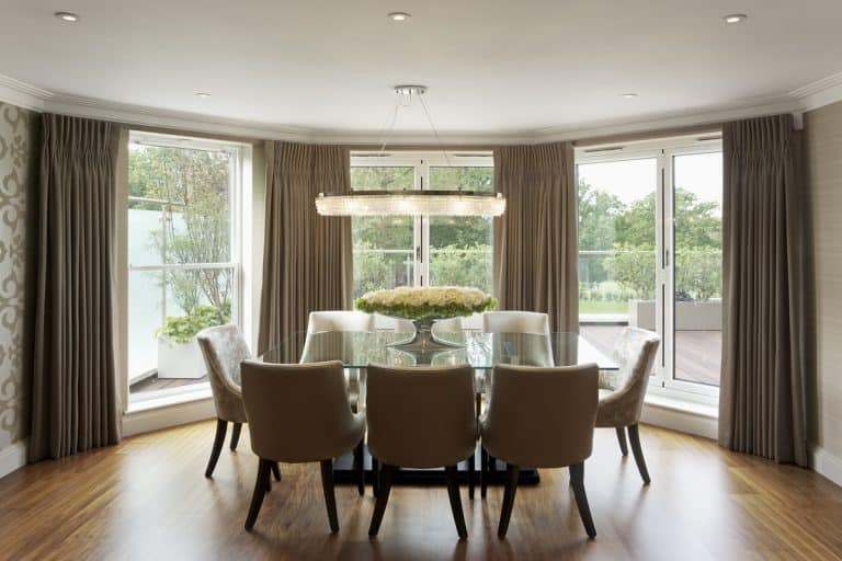 A dining are with brown classic designed dining chairs and a bay window with cream colored curtains, What Curtains Look Best On Bay Windows?