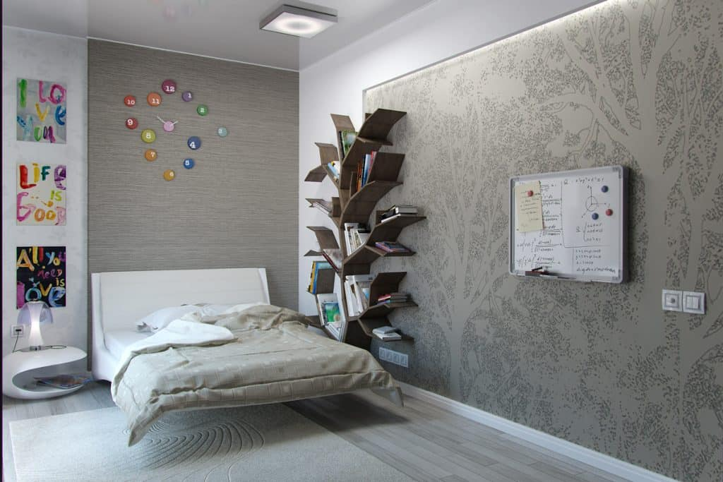 A gray themed bedroom with and accent wall on the side and a tree themed bookshelf