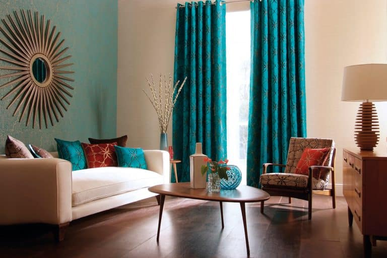 A home interior showcase with the incorporation of blue curtains against cream colored walls and added with the brown texture of wood laminated flooring, How to Remove Mold From Curtains [5 Steps]