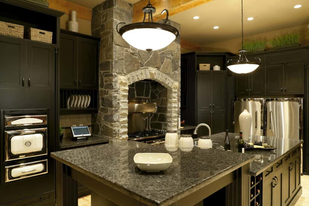 A kitchen with marble countertops, faux stone decorative walls, and black paneled cabinets