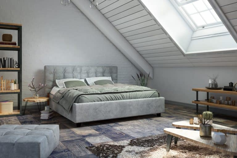 A loft bedroom with white painted walls, gray bedding sets, and different textured tiles, Can Bedrooms Have Different Flooring?