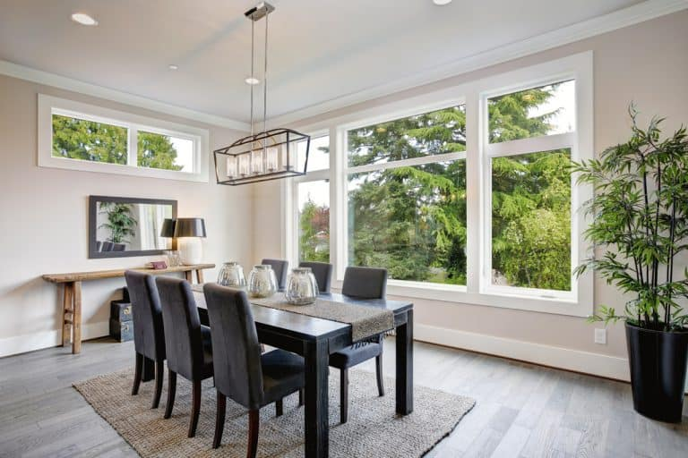 A luxurious modern architecture masterpiece with its dining room properly lit by the huge windows and a chandelier, What Is The Best Lighting For A Dining Room?
