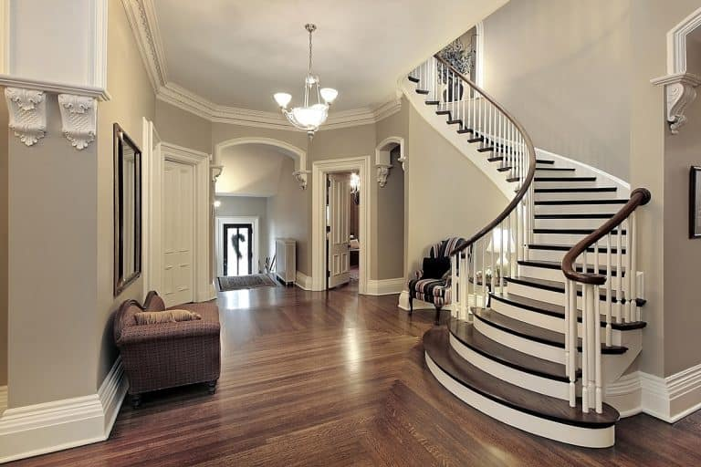 A luxurious looking foyer with a curved staircase and a matching wooden vinyl flooring, How to Decorate a Long and Narrow Entryway [7 Suggestions]
