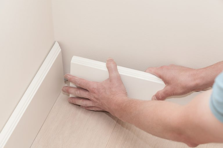 A man holding a white colored baseboard and placing it to find the angle for the 45 degree cut, 5 Types Of Baseboards For Your Home