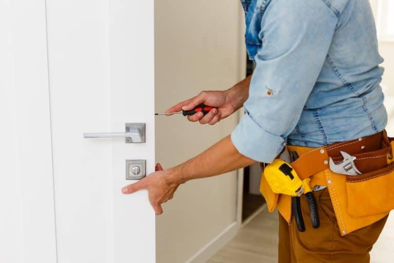 A man installing a door lock on a bedroom door, Should Bedroom Doors Have Locks?