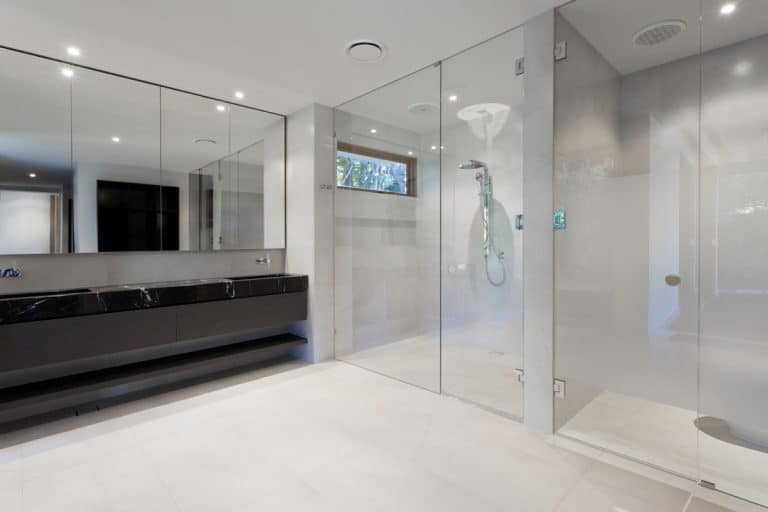 A modern bathroom with a dark marble countertop in the lavatory section and frameless shower door, Do Frameless Shower Doors Leak?