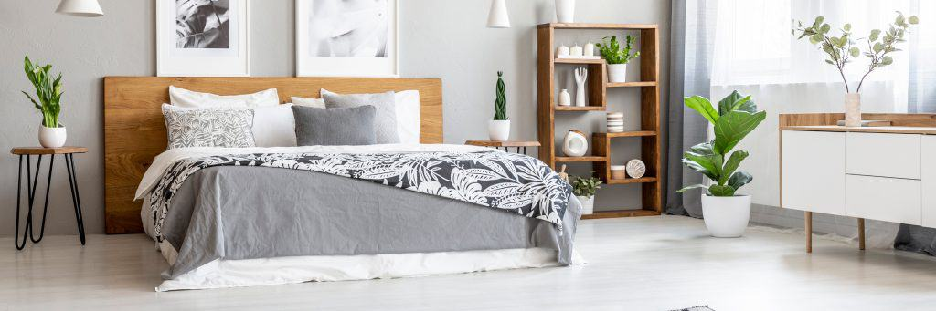 A modern bedroom with a hardwood headboard with matching gray colored bedding sets and a nightstand with a plant placed on top of it