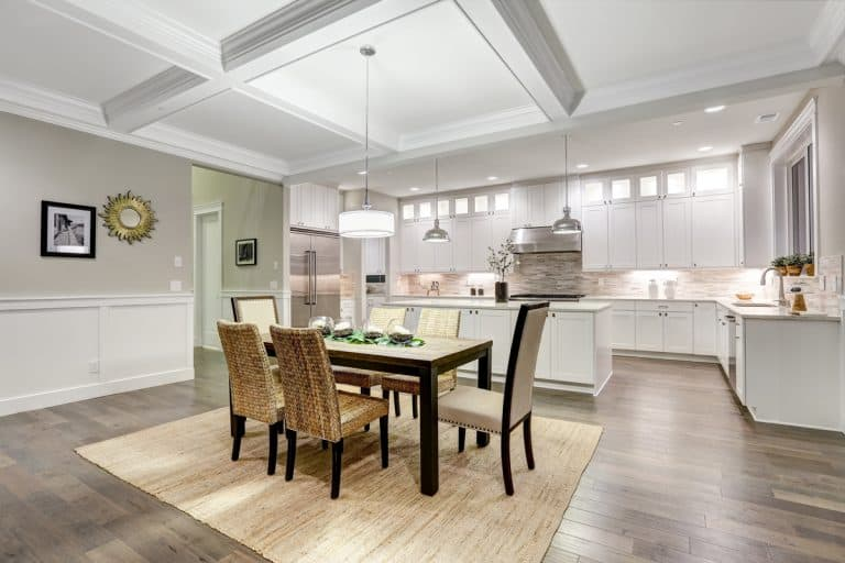 A modern dining room with handcrafted wicker chairs place on top of a brown rug, Should You Have A Rug In The Dining Room?