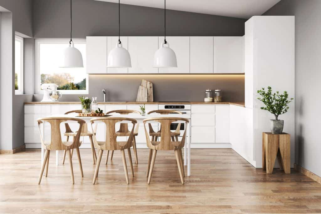 A modern farmhouse themed kitchen with wooden dining chairs, wooden laminated flooring, and white colored cabinet panels
