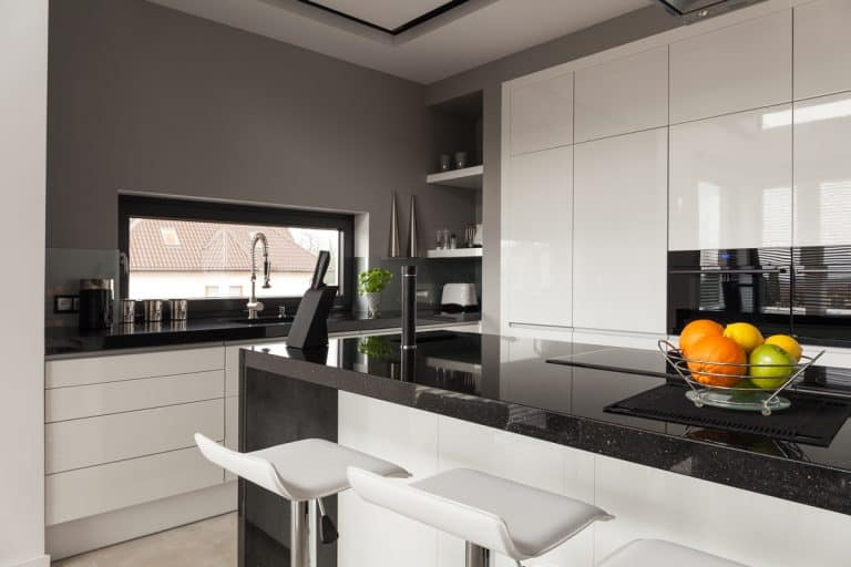 A modern kitchen with white paneled cabinets mixed with black granite countertops, What Color Cabinets with Black Granite Countertops?