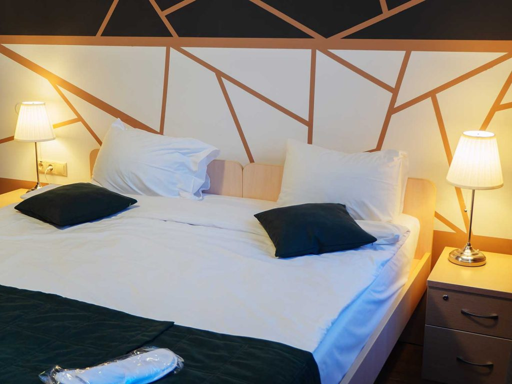 A neat double bed with lit floor lamps on the nightstands and a geometric pattern on the wall