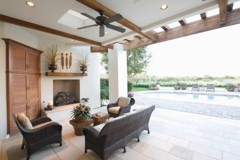 Tropical house with an outdoor pool, rattan chairs, a white painted ceiling with a black colored ceiling fan, Should the Ceiling Fan Match the Ceiling Color?