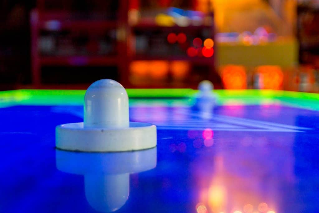 An up close photo of a blue colored air hockey table at an arcade