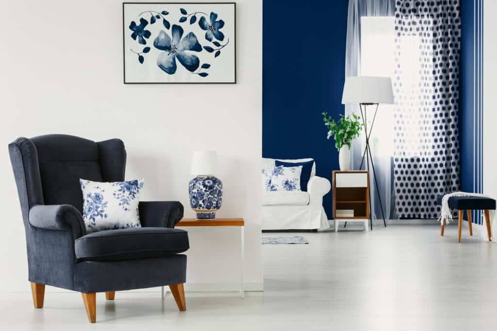 A white and blue themed living room with blue curtains, and an accent wall on the background