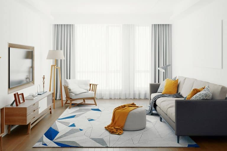 A white modern living room with gray curtains and white drapes matched with a gray sofa with an ottoman on top of the rug, Do Curtains Usually Drop After Hanging?