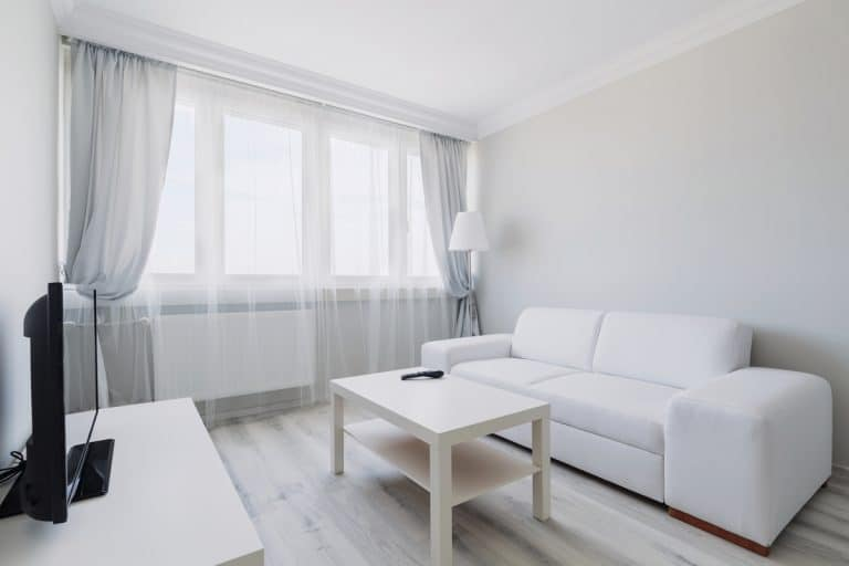 A white themed living room with white couches, white walls, and white curtains, Can Curtains Make A Room Look Smaller?