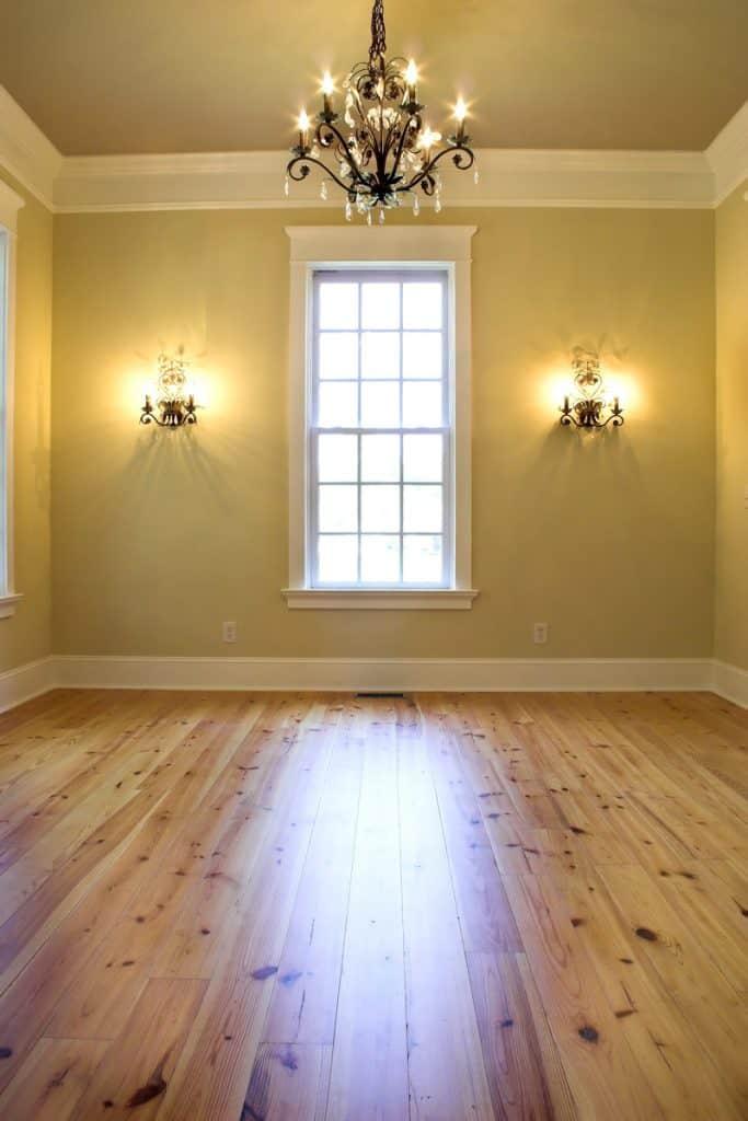 Süslü duvar lambaları ve şık bir avizesi olan boş bir bej oturma odası