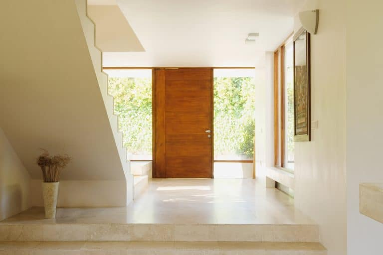An empty foyer with a hardwood pivot door, white colored walls and ceiling, and a stairway on the side, How To Decorate A Living Room With No Entryway