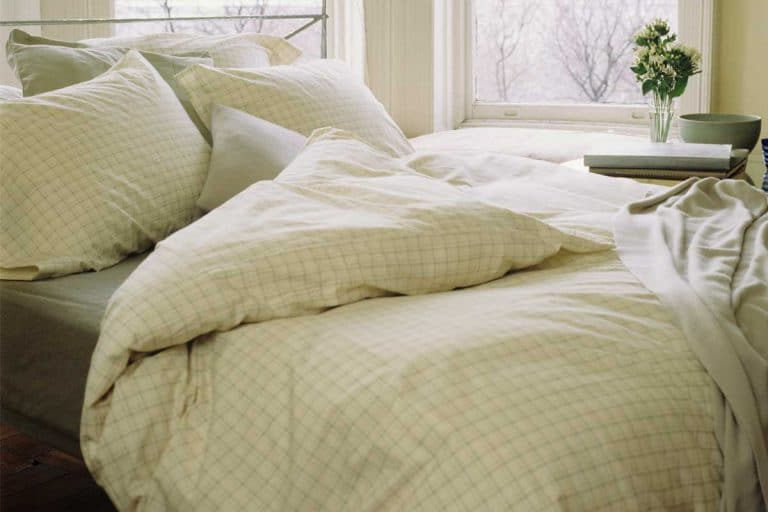 Bed with pillows, linens and comforter beside window, 16 Different Types Of Comforters