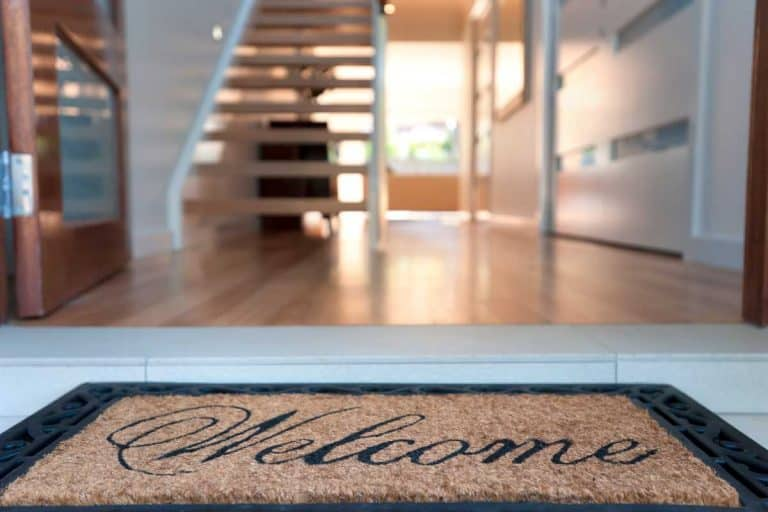 Close up of a welcome mat in front of an inviting house