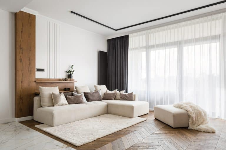 Elegant and comfortable designed living room with big corner sofa, wooden floor and big windows, what curtains to use with traverse rods