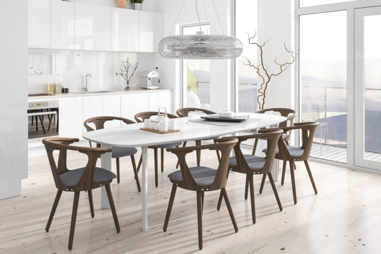 A luxurious modern dining room with wooden dining chairs, white granite table, a huge window for natural lighting, and white paneled cabinets, How To Fill Empty Space In Dining Room [5 Awesome Ideas!]