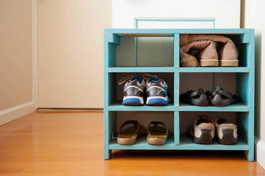 Shoes on a blue rack, shot on a wood floor with soft light and negative space.