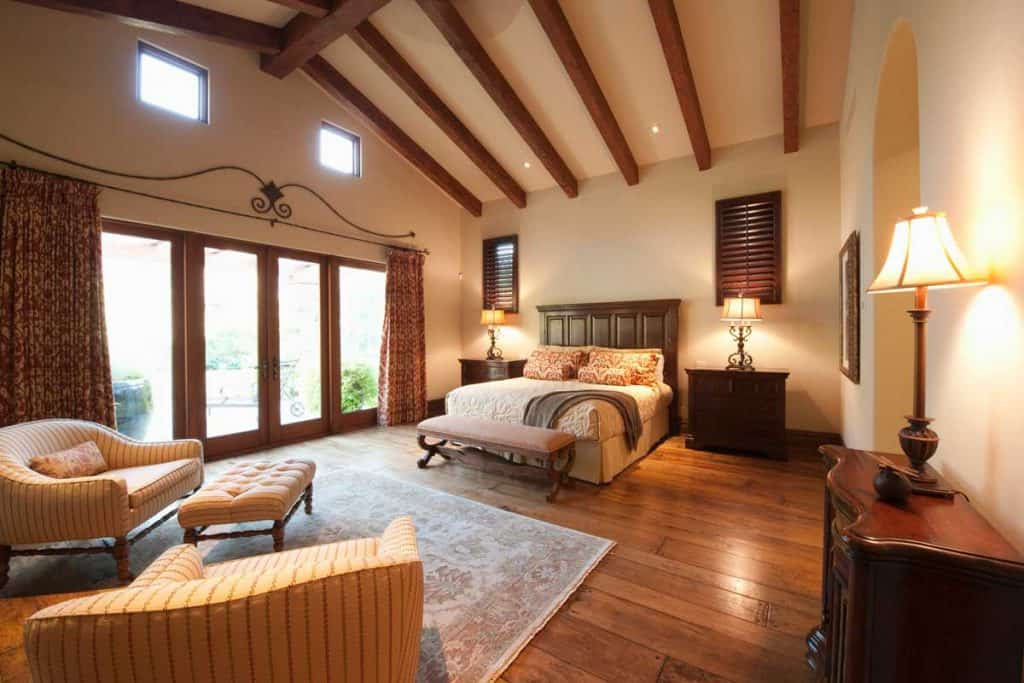 Spacious bedroom with beamed wooden ceiling, How to Make Ceilings Look Higher? [5 Practical Solutions]