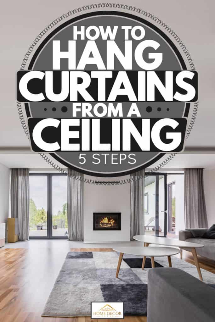 A modern living room with laminated vinyl flooring, checkered rug gray sofas, and gray ceiling curtains with a fireplace on the middle, How to Hang Curtains from a Ceiling [5 Steps]