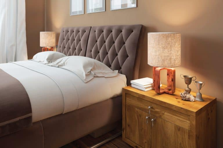 Wooden bedside tables with expressive textures in a modern bedroom, should headboard be against wall
