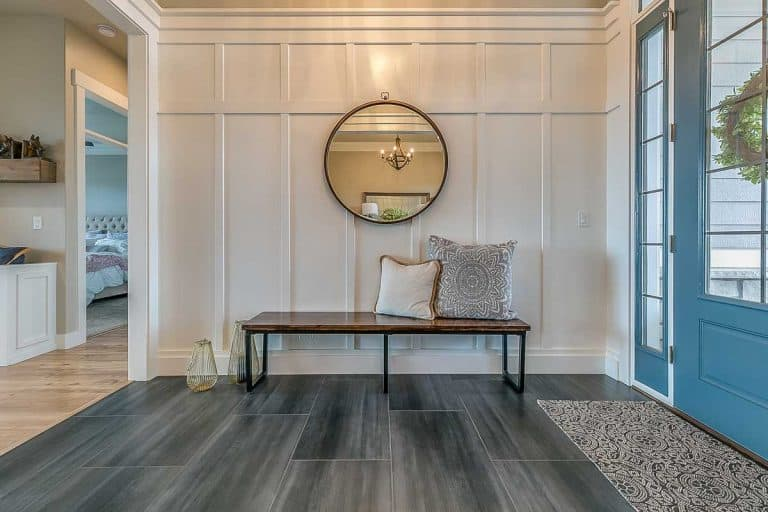 round mirror on the wall with wainscoting and beautiful blue front door, How Tall and Wide Should an Entryway Bench Be?