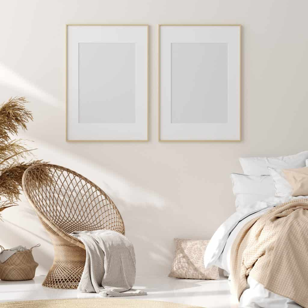 A beige painted wall with beige rattan basket like chairs and a bed with beige beddings