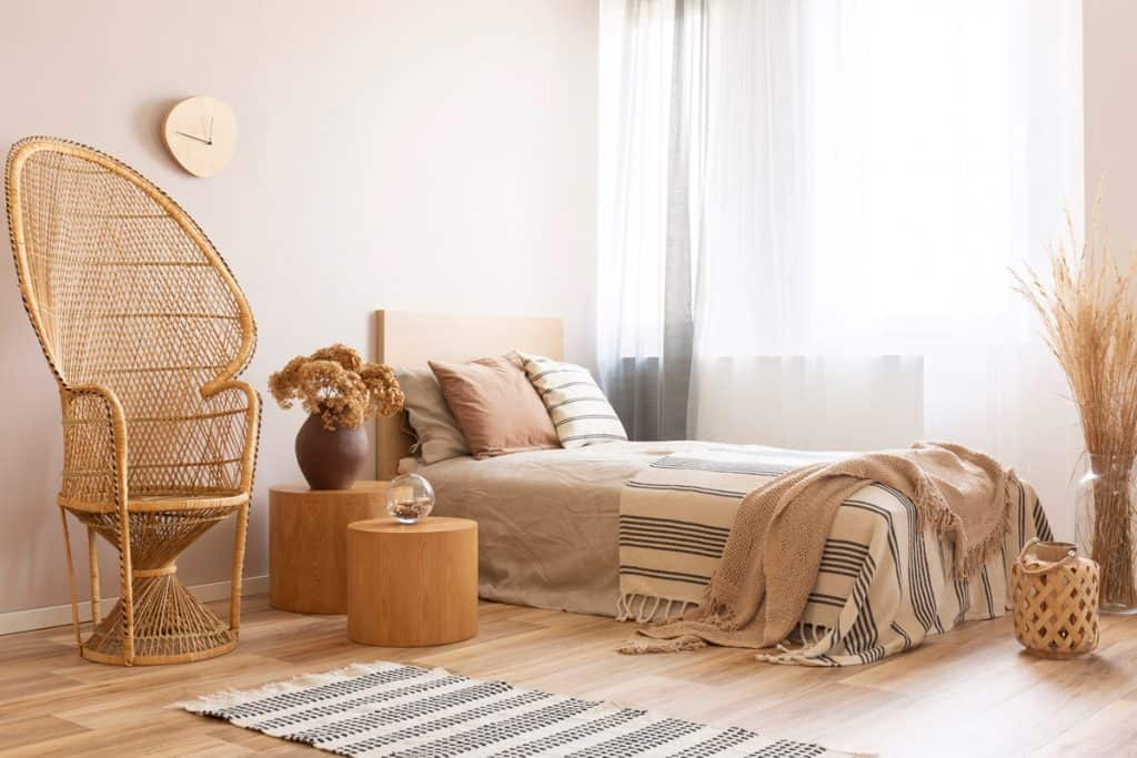 A beige painted wall with white curtains and a beige color bedding set