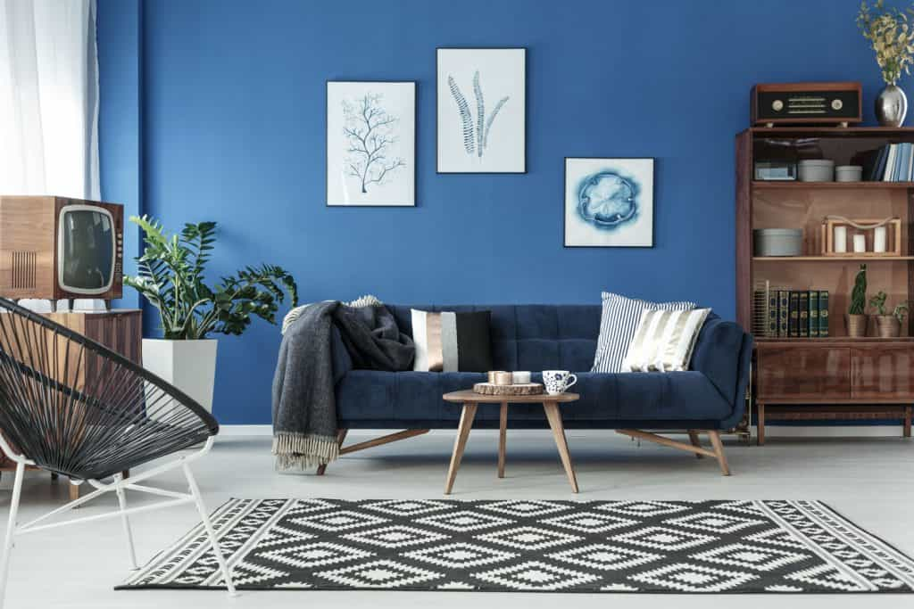 A blue colored wall with a dark blue colored chair and checkered rug on the center of the living room