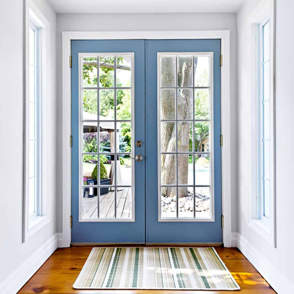 A blue French door leading to the patio