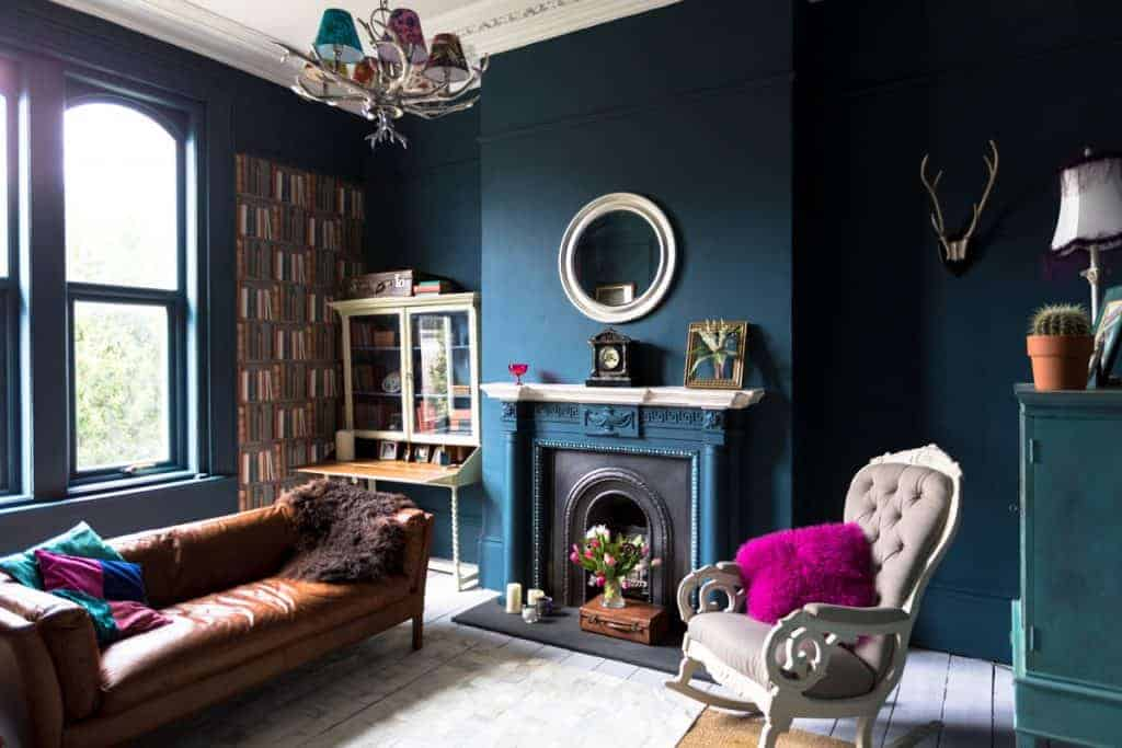 A blue painted living room with a blue colored fireplace mantel inforporated with a brown sofa