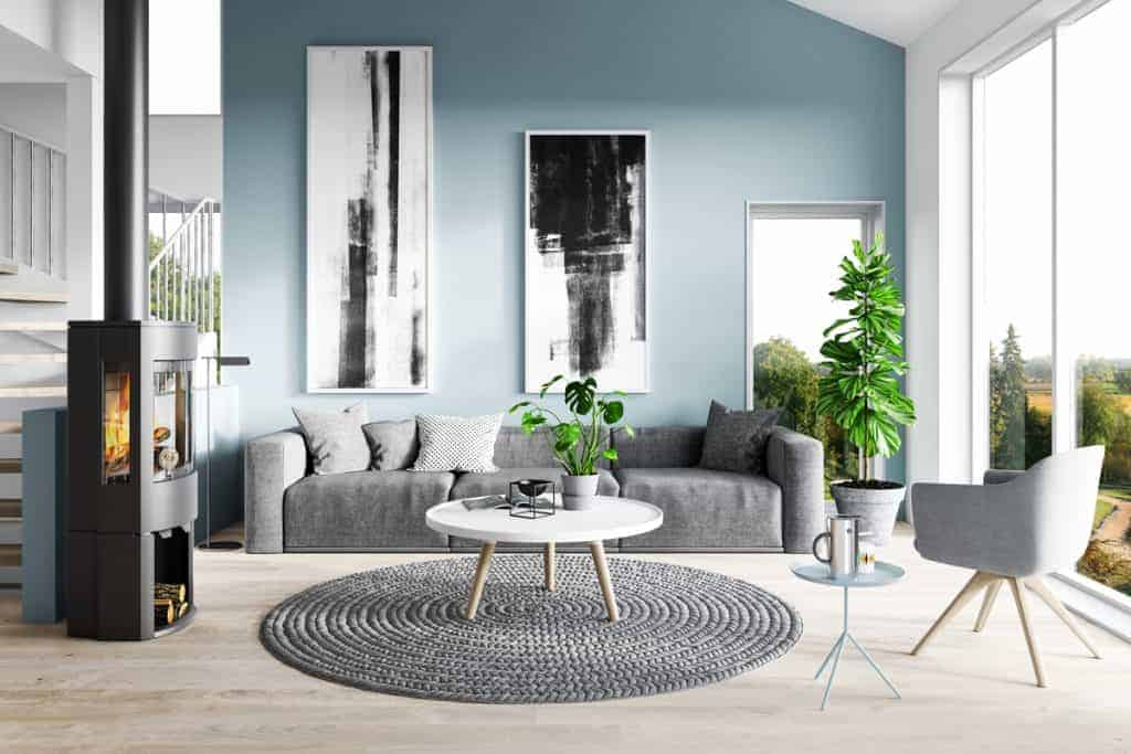 A blue painted wall on a luxurious living room with gray colored furnitures matched with indoor plants near the huge window