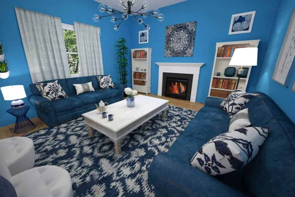 A blue themed living room with blue furnitures, blue area rug, and a matching fireplace mantel