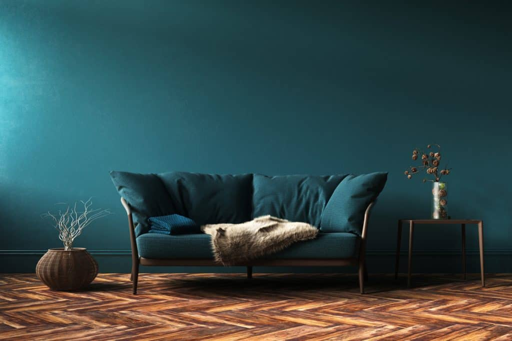 A blue themed living room with a bluish green colored couch and a zigzag patterned carpet