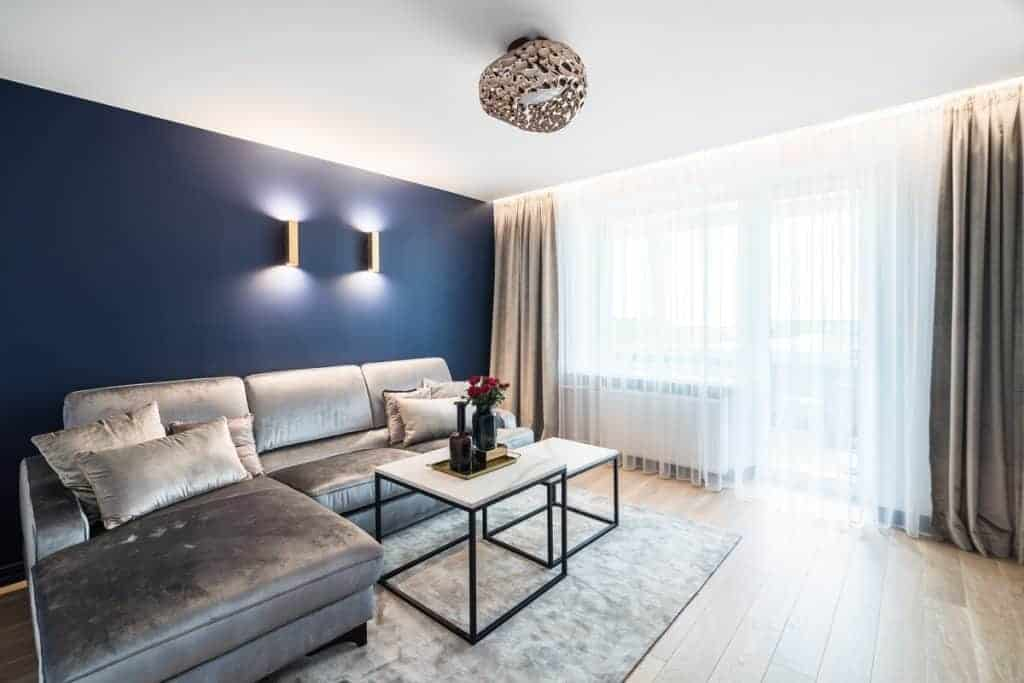 A blue walled living room with cool wall lamps, gray curtains with white drapes and an area rug with gray sofas