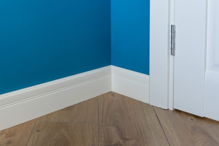 A blue walled room with a white colored baseboard and a wooden floor, What Is The Best Paint For Baseboards? [4 Actionable Suggestions]