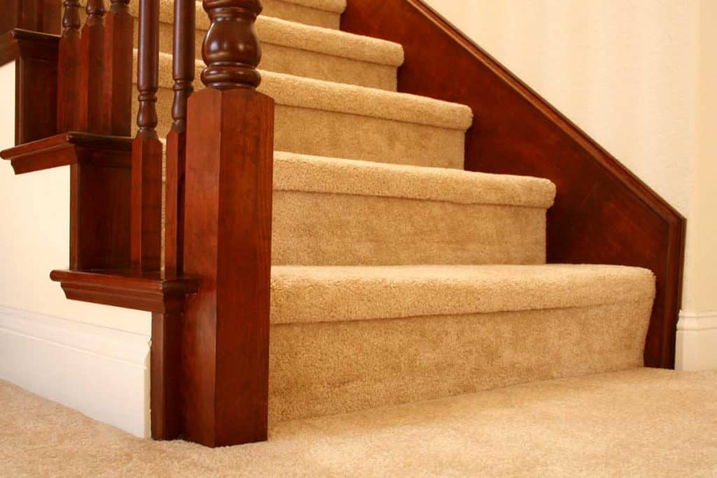 A carpeted staircase going to the second floor