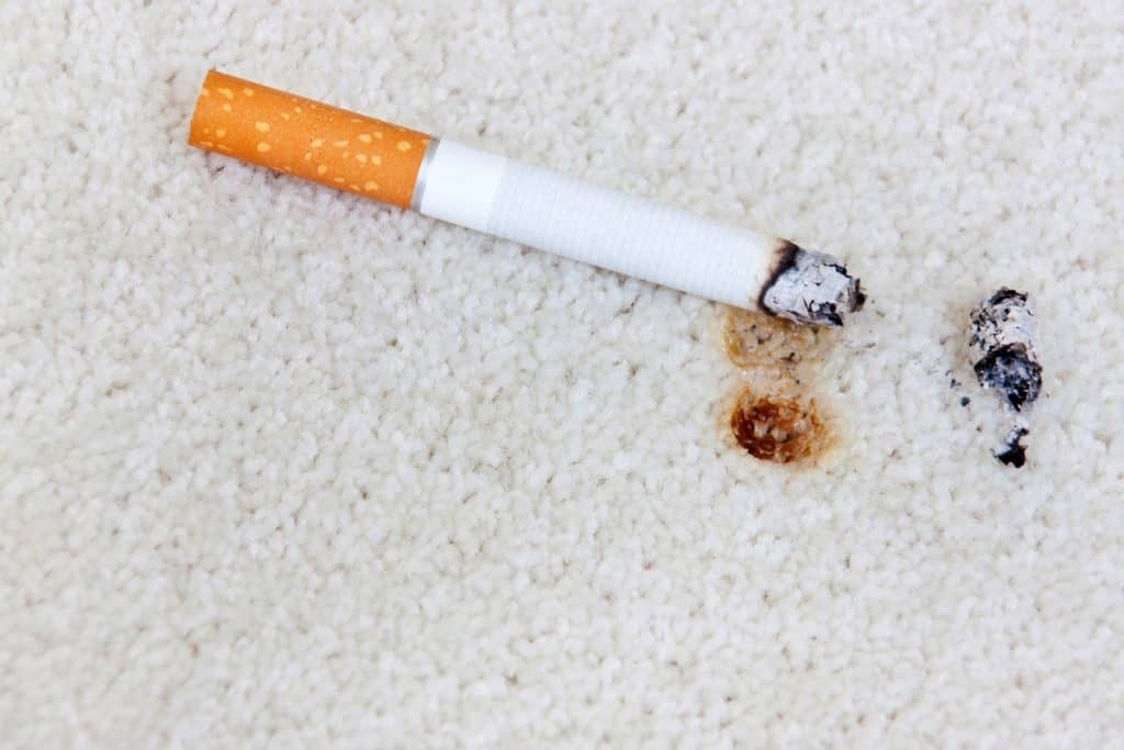 A burn on the carpet caused by cigarette