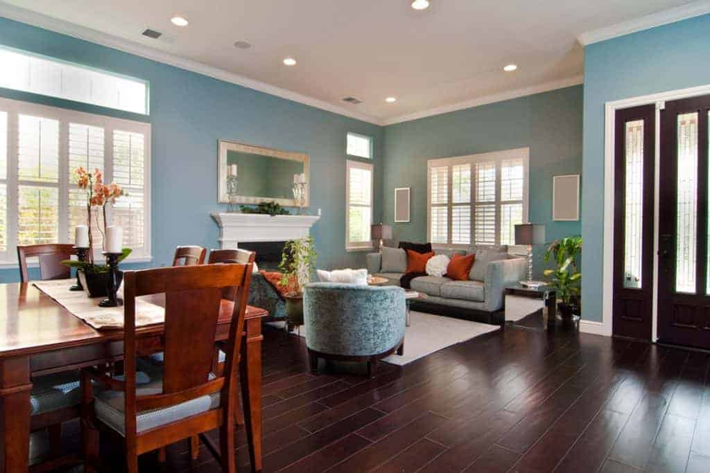 A comfortable living room with wooden flooring, light blue colored furnitures, and a wooden dining set