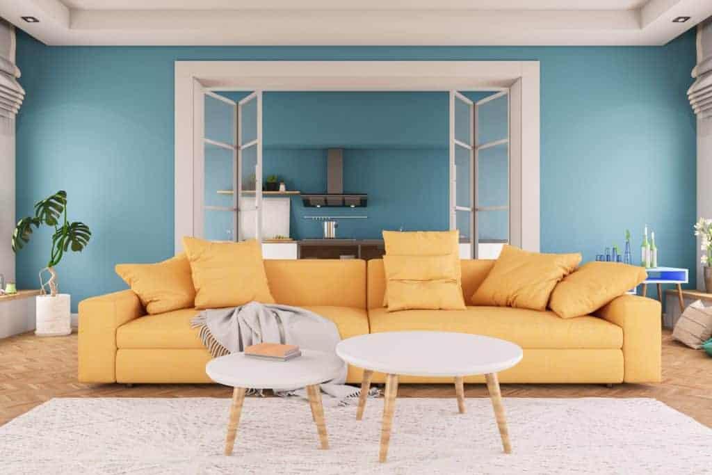 A comfy blue painted living room with a yellow sofa, a white area rug, and a white round table